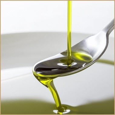 Olive Oil pouring from metal spoon